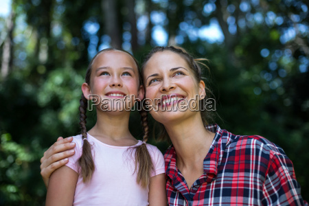 cheerful mother with daughter looking up