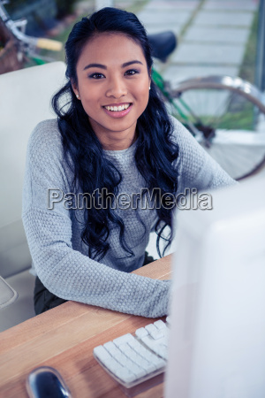 smiling asian woman using computer and