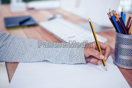 womans hand drawing with pencil on