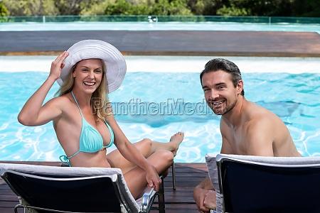 happy couple sitting on sun lounger