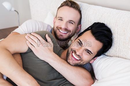 happy gay couple lying on bed