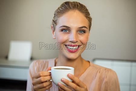portrait of happy woman holding coffee