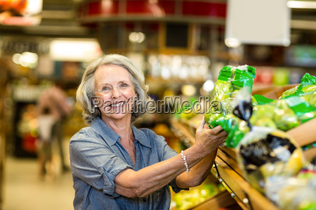 senior happy woman holding bag of