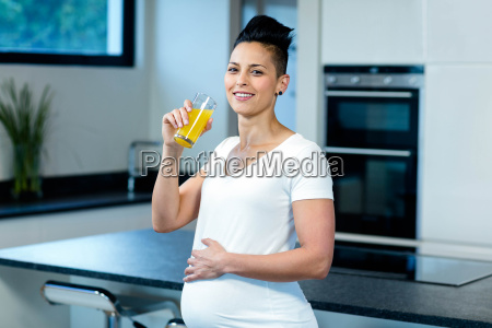portrait of pregnant woman drinking juice