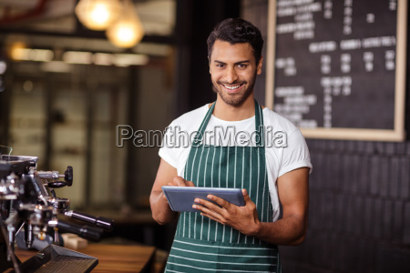 smiling barista using tablet and looking