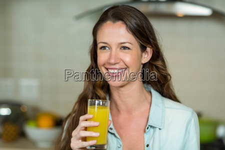 young woman smiling while drinking juice