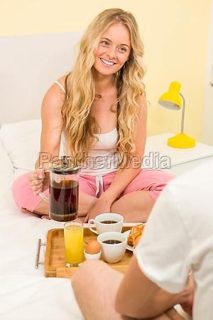 cute couple having breakfast sitting on