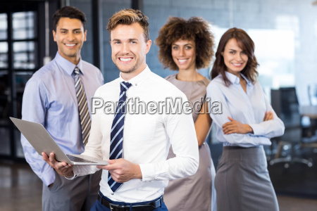 businessman standing with a laptop and
