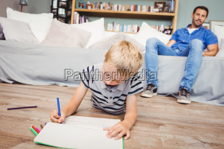 boy drawing in book while father