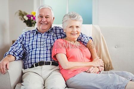 senior couple sitting on sofa and