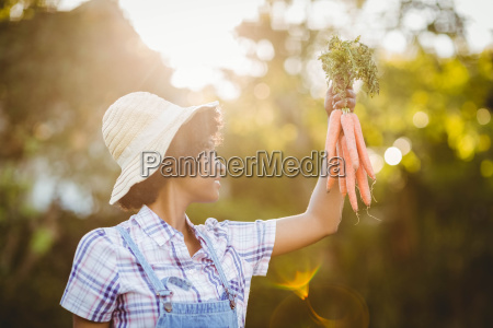 smiling woman holding carrots