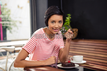 smiling woman eating a chocolate cake