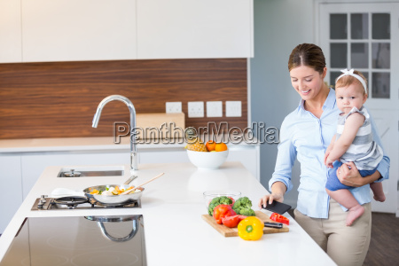 woman carrying daughter by kitchen counter
