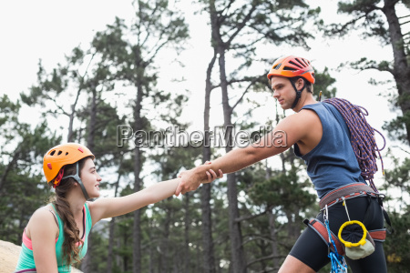young couple holding hands at forest