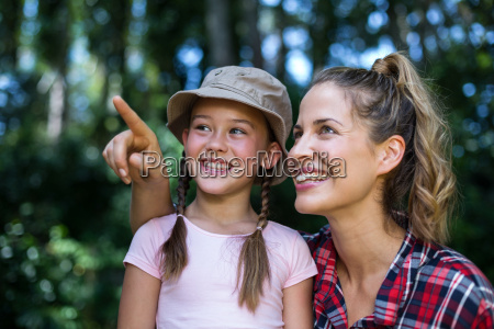 happy mother pointing up by daughter