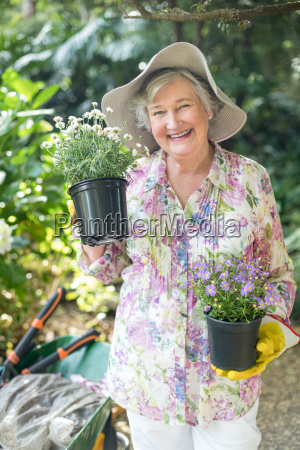 portrait of senior woman holding potted