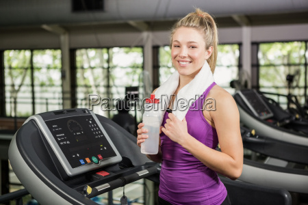 woman on treadmill holding water bottle