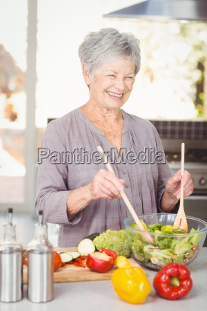 happy senior woman tossing salad while