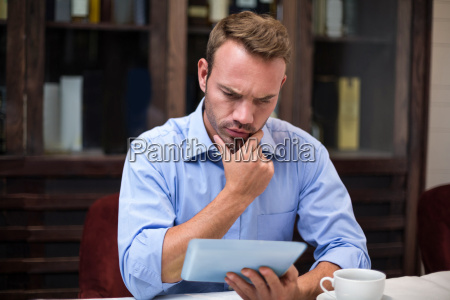 serious businessman using digital tablet