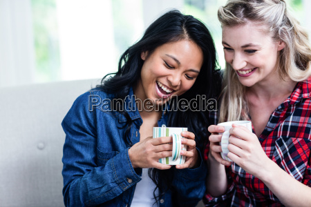 happy young female friends drinking coffee