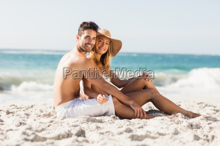 young couple sitting on sand