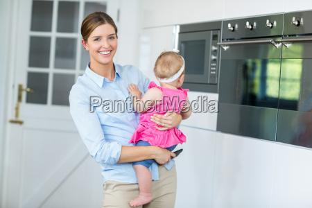 woman carrying baby girl in kitchen