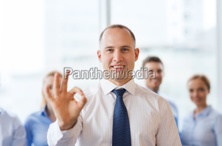 smiling businessman showing ok sign in
