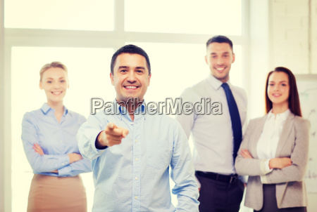 businessman in office pointing finger at