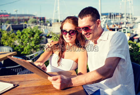 smiling couple with menu at cafe