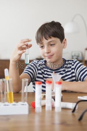 happy boy holding test tube at