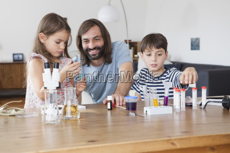 father and children doing science experiment