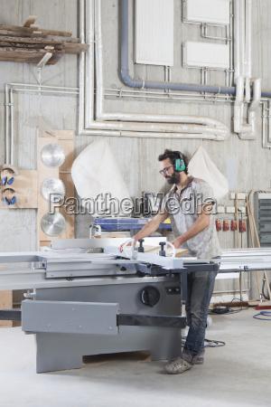 full length of male carpenter using