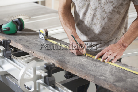 midsection of male carpenter measuring plank