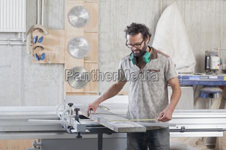 male carpenter measuring lumber in workshop