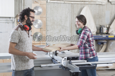 carpenters laughing while using sliding table