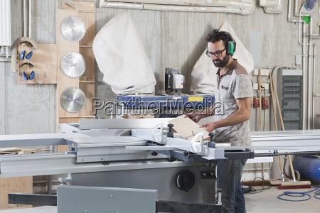male carpenter using a sliding table