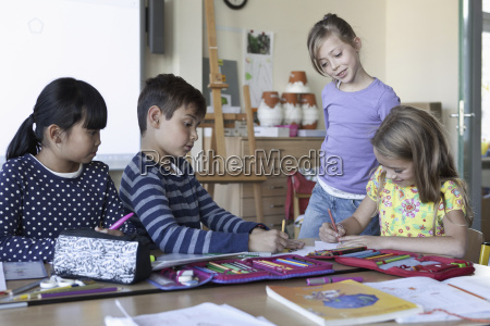 students drawing on paper in classroom
