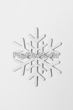 close up of snowflake against white