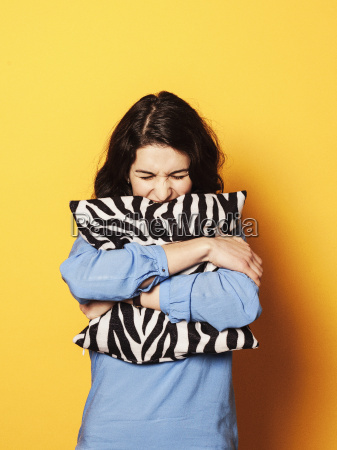 irritated young woman embracing cushion against