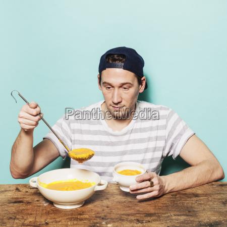 mid adult man serving pumpkin soup