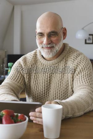 mature man using digital tablet on