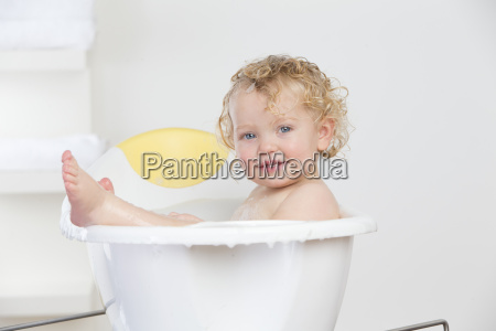 smiling baby sitting in bathtub
