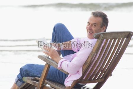 older man reading book in deck