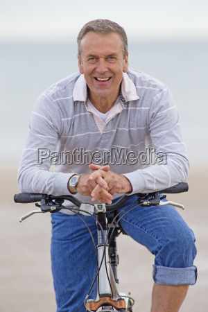 older man riding bicycle on beach