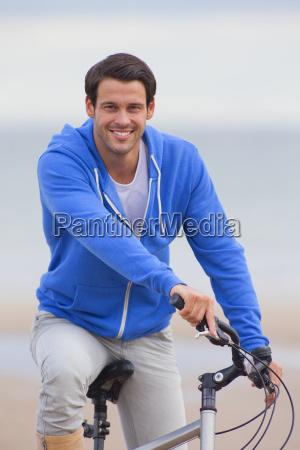 smiling man riding bicycle on beach