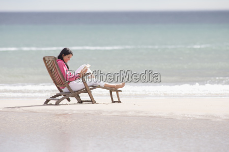 woman reading book in deck chair