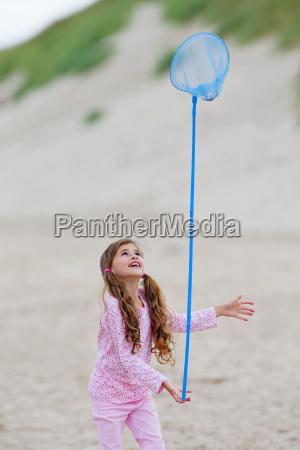 girl balancing butterfly net on finger