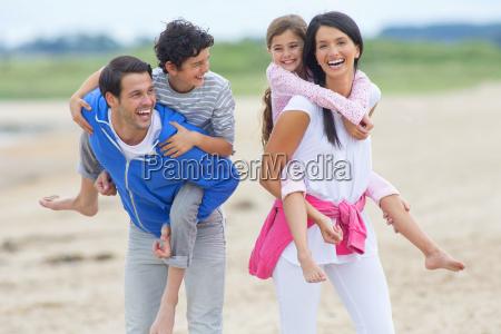 parents carrying children piggyback on beach