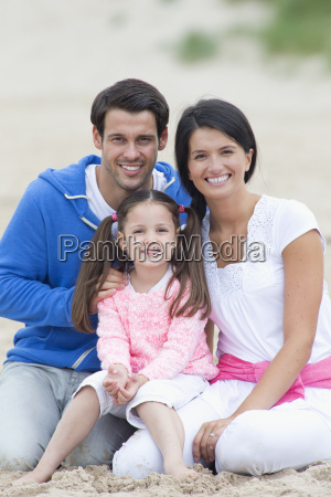 parents and daughter smiling together on