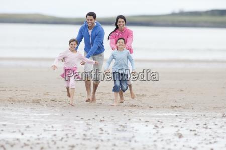 parents chasing children on beach